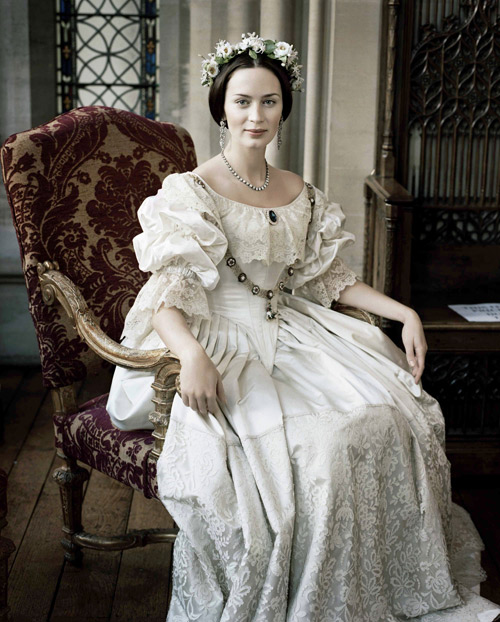 A photo from the film of Queen Victoria's Wedding Gown with a recreated St George's Chain and Sapphire brooch and diamond necklace and earrings